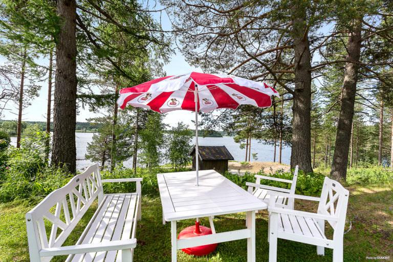 Bort och parasoll med utsikt över vattnet mellan tallarna.