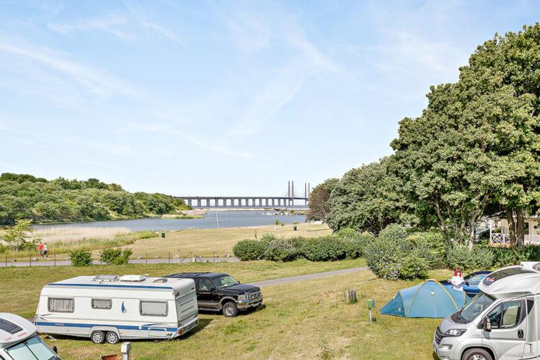 Husvagn och husbil, samt tält med utsikt över Öresundsbron.