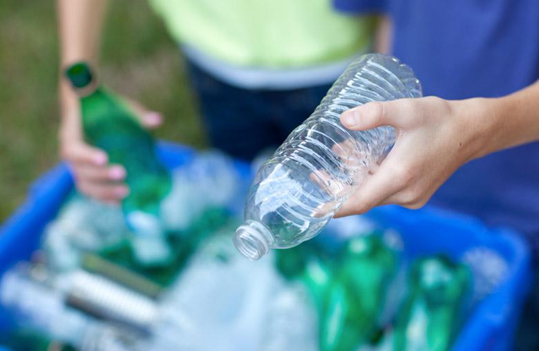 personer källsorterar plats och glas i återvinningsbehållare