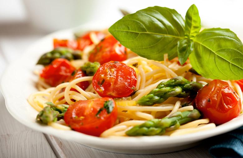 pasta med tomater och sparris i vit skål
