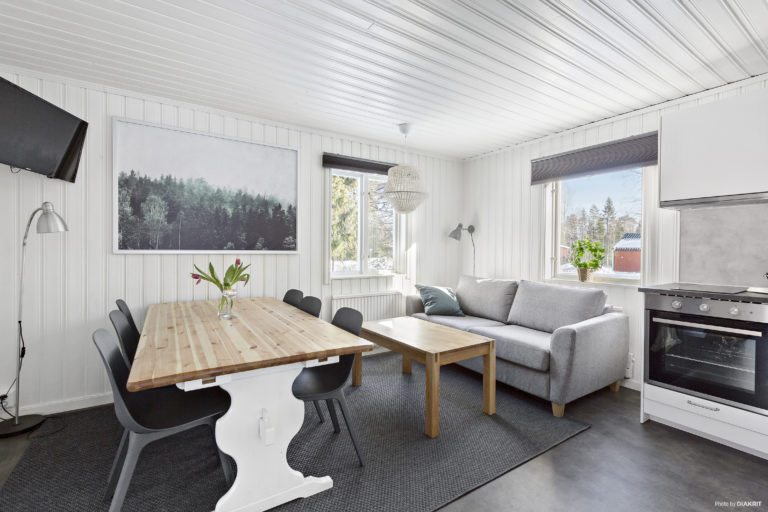 vardagsrum i ljusa färger med matbord, soffa och tv, öppen planlösning till det moderna köket
