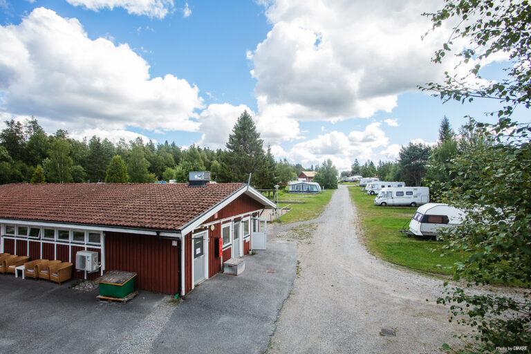 rött hus på camping med husbilar och husvagnar i bakgrunden
