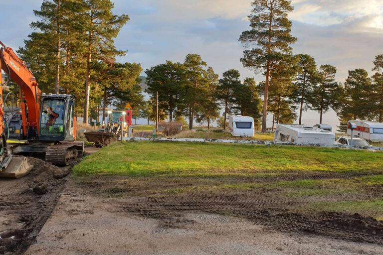 grävskopor utför markarbete på camping i solnedgång med husvagnar i bakgrunden