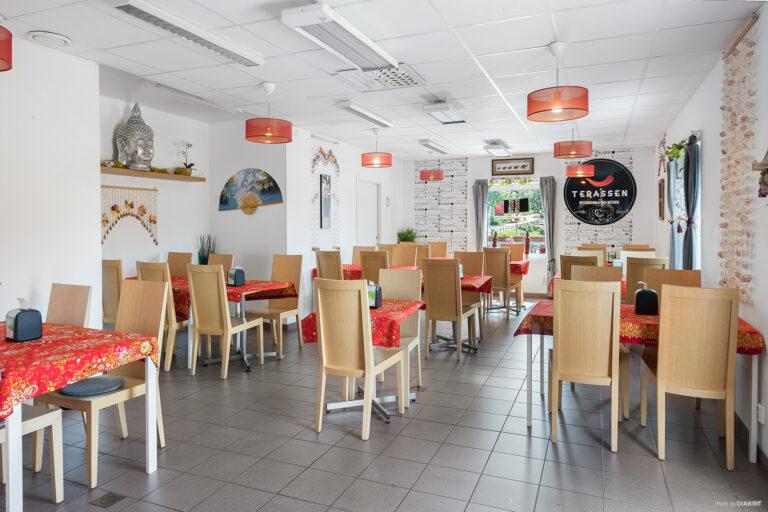 restaurang interiör vita väggar och stolar och bord i trä