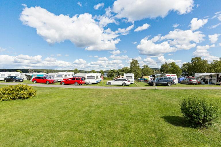 husvagnar uppställda på stor gräsyta med utsikt över sjö