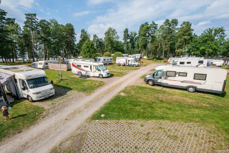 husbilar uppställda på campingområde vid sjö